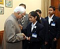 Children supported by National Foundation for Communal Harmony pinning a flag on the Vice President, Shri Mohd. Hamid Ansari, in New Delhi on November 25, 2014.jpg