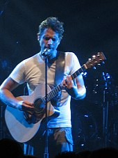 A man wearing a white T-shirt, playing a guitar with his eyes closed while standing behind a microphone stand.