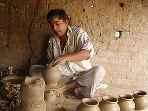 Gujrat City - A clay artist working thrower to make terracotta vases.