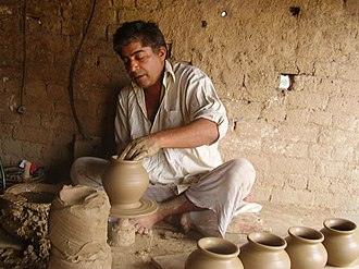Gujrat, Pakistan - A clay artist working thrower to make terracotta vases.