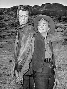 A man and a woman stand near each other, both wearing Western cowboy outfits. They are both smiling, as they stand in what appears to a movie set.