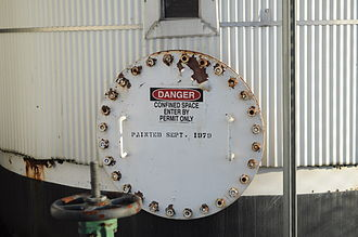 Confined space rescue - A warning label on a storage tank, indicating that it is a confined space.