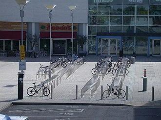 Вид с большой высоты на четыре ряда десятков U-образных стоек, установленных в бетоне перед зданием со стеклянным фасадом, с парковочными местами для инвалидов на переднем плане.