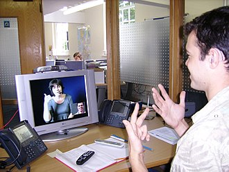 Video relay service - A deaf or hard-of-hearing person at his workplace using a VRS to communicate with a hearing person in London.