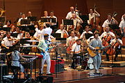 Five members of a band play keyboards, electric bass, drums and guitar in front of a symphony orchestra and its conductor, all dressed informally.
