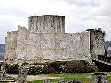 A tall pale grey wall around an enclosure and surrounded by a ditch. A modern metal bridge leads up to the entrance between two towers in the wall. A square stone tower rises above the wall.