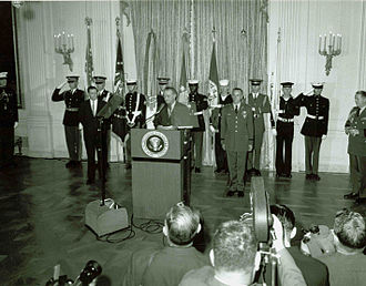 Roger Donlon - Donlon (standing at right, at attention) waits to receive his Medal of Honor from U.S. President Lyndon B. Johnson.
