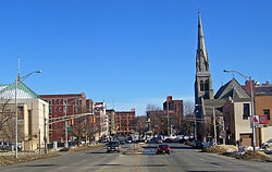 A view from the middle of an urban street looking toward a square some blocks away where a monument stands on a tall pedestal, in winter. Buildings of several stories in height line the street on either side; on the right is a church with a tall steeple.