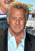 Photo of Dustin Hoffman--a 74-year-old white man with gray hair, small eyes and a big nose, wearing a black blazer over a light blue casual shirt--attending the French premiere of his film, Quartet, in 2013.