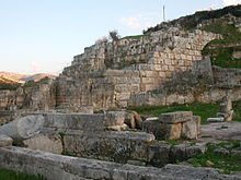 A wall made at its lower part of tightly packed white limestone stone blocks surmounted by a wall constructed of very large rusticated ashlar.