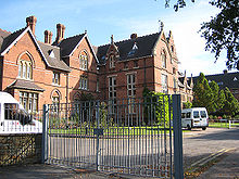 A large brick building with metal gates in front of it; a fence and some trees in the foreground.