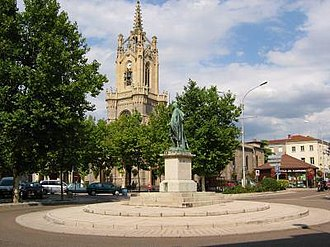 Feurs - The church with a statue of Michel Combes in the foreground