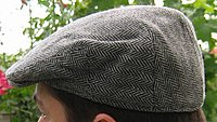 A grey wool flat cap on a man's head.