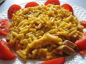 Macaroni and cheese - A plate of pre-packaged Kraft macaroni cheese, served with tomato and sausage