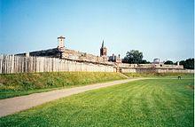 Fotografia di un campo erboso e di una palizzata di tronchi.  Le cime degli edifici in legno sono visibili dietro la palizzata.