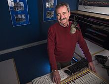 An older man with salt-and-pepper hair and a mustache stands smiling in a radio station. He is wearing a burgundy sweater.