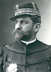 Driekwart zwart-wit foto van een man in militaire kleding, donker haar, dikke snor en baard die wit begint te worden, met een medaille aan de rechterkant van zijn borst