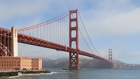 The Golden Gate Bridge on an early morning in June 2017 as seen from the Fort Point side. The sun slowly dissolves the fog that's covering the Marin Headlands and parts of the bridge.