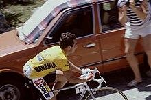 Color photograph of Hinault on his bike, climbing a mountain while wearing a yellow jersey