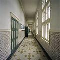 Interieur, overzicht van een gang met een lambrisering van geglazuurde tegels en tegelvloer - 's-Gravenhage - 20387478 - RCE.jpg