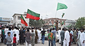 Pakistani general election, 2013 - A supporter of PMLN in NA 49 Islamabad, in Model Town Hummak, on the roof of a car rising his party flag and announcing the triumph of his party in that area