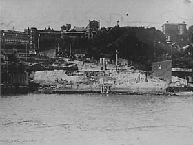 Photograph shows construction on the foreshores of Kirribilli above Jeffrey Street circa 1930. St. Aloysius College incorporating Dr. Cox's home and the tower of Star of the Sea Church are visible on the skyline. The homes Greencliffe and Craiglea are also visible on the right hand side above M. Steel boatshed