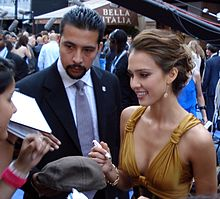 Smiling young woman with wavy hair pulled up in a loose bun, wearing a gold low-cut dress and accompanied by a man. She is signing autographs.