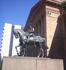 Equestrian statue in dark grey metal of George V in military dress uniform on a plinth of red granite outside a Classical building of red sandstone