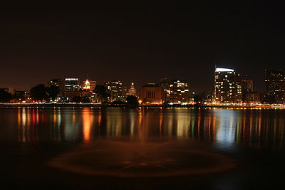 The skyline of a city seen at night from across a lake