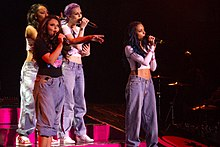 Four young women singing on a stage in front of a crowd. The women are wearing baggy trousers while singing into a microphone with their other hand as bright pink stage lighting shines upon them.