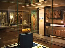 View of the Cyrus Cylinder in its display cabinet, situated behind glass on a display stand. Other ancient Persian artefacts can be seen lining the room in the background.
