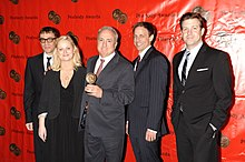 From left to right, Fred Armison, Amy Poehler, Lorne Michaels, Seth Meyers, and Jason Sudeikis stand in a line. Michaels holds an award.