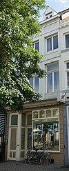 foto van Huis met gepleisterde lijstgevel, voorzien van segmentboogvensters en een uitgebouwde erker op de verdieping.