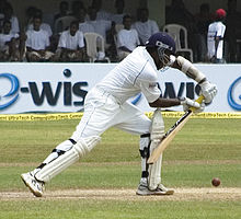 A man standing on a cricket pitch, wearing white cricket kit and blue helmet leans forward to play the ball with a bat held out in front. The seating area of the ground is visible in the background.