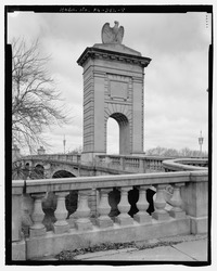 A stone arch with stone eagle is in the background near the entrance to a bridge that continues beyond it. A stone banister and railing in the foreground.