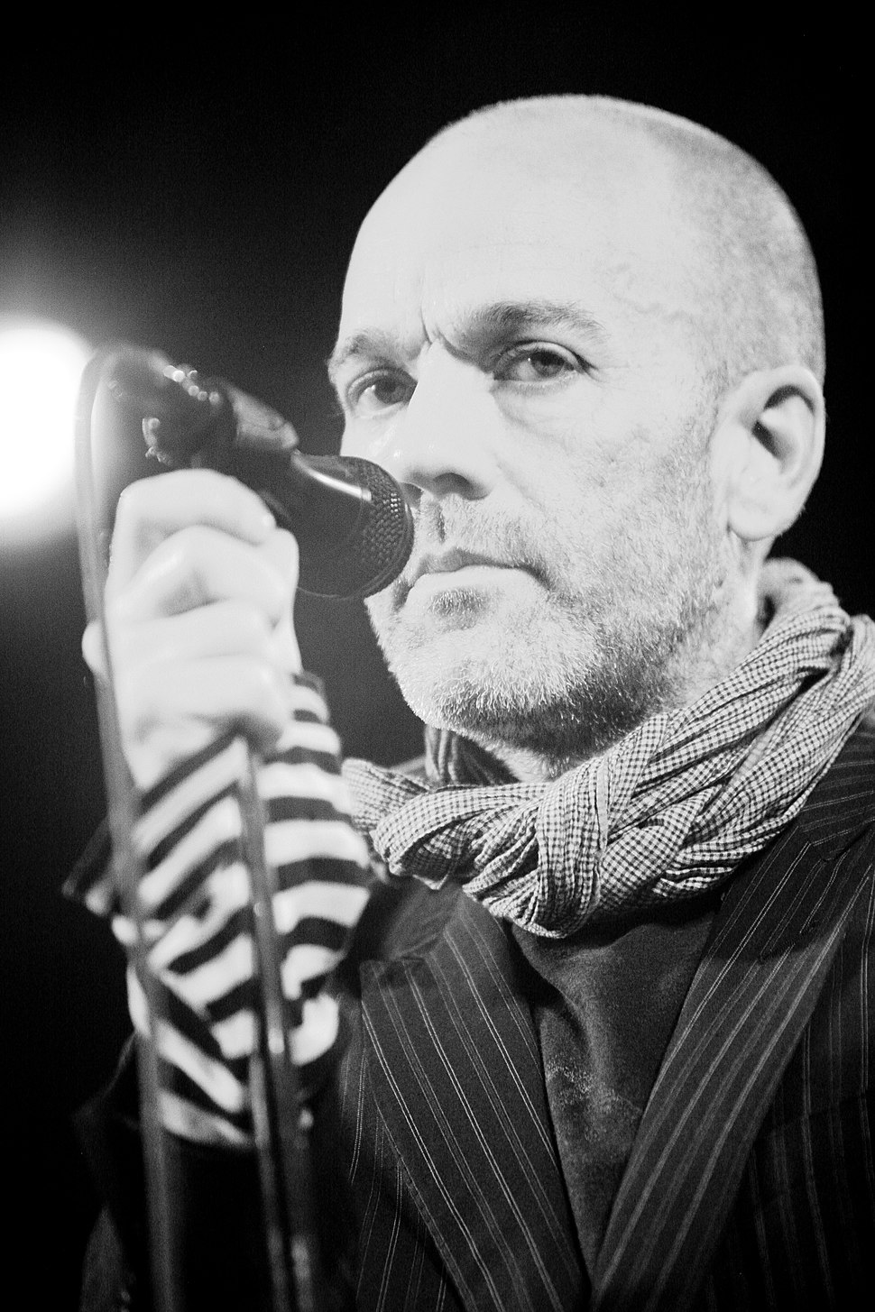 A close-up of Stipe holding a microphone
