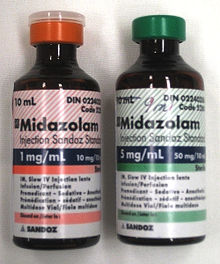 Two 10 ml bottles labeled Midazolam  - the bottle on the left has a label in red and says 1 mg/ml; the one on the right is in green and says 5 mg/ml. Both bottles have much fine print.
