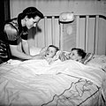 Mrs. Jack Wright tucking her two sons, Ralph and David, into bed at the end of the day, Toronto, Ontario - Mme Jack Wright bordant ses deux fils, Ralph et David, à la fin de la journée, Toronto (Ontario).jpg