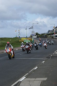 Several motorcycle riders racing on a public road