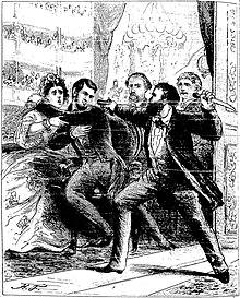 Dans une loge de théâtre, un homme barbu armé d'un couteau dans sa main gauche pointe de sa main droite un pistolet sur la tête du président Lincoln, qui se recule dans les bras de sa femme.