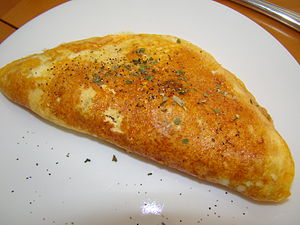 English: An omelet with ham, cheese, and a gar...