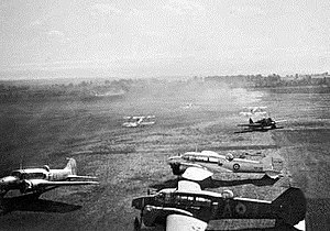Three twin-engined military monoplanes parked on a landing field, with other aircraft in the background