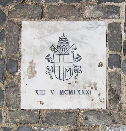 Small marble tablet in St. Peter's Square indicating where the shooting of John Paul II occurred. The tablet bears John Paul's personal papal arms and the date of the shooting in Roman numerals. PapalAssassinationAttemptMarker.jpg