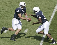 Penn State Nittany Lions quarterback #14 Anthony Morelli hands the ball off to his tailback #33 Austin Scott in their 2007 season opener.