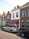 foto van Gepleisterde lijstgevel voor huis van parterre en verdieping onder schilddak waarin dakvenster met vleugelstukken