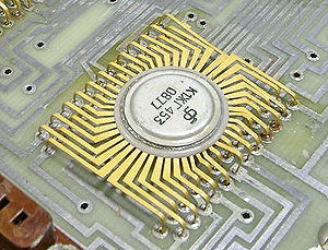"Integrated circuit packaging - Early USSR made integrated circuit. The tiny block of semiconducting material (the ""die""), is enclosed inside the round, metallic case (the ""package"")."