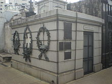 Photograph showing a mausoleum building of gray ashlar construction with metal wreaths and plaques attached to the outside walls, a metal barred gate at the entrance and surmounted by a square cupola