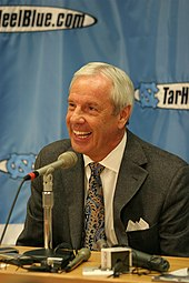 A man with short gray hair wearing a suit smiles in front of a microphone