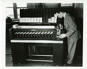 Radix sort - An IBM card sorter performing a radix sort on a large set of punched cards. Cards are fed into a hopper below the operator's chin and are sorted into one of the machine's 13 output baskets, based on the data punched into one column on the cards. The crank near the input hopper is used to move the read head to the next column as the sort progresses. The rack in back holds cards from the previous sorting pass.