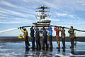 Sailors and Marines hoist a fire hose over their heads as they wash the flight deck of the aircraft carrier USS Nimitz (CVN 68) as the ship operates in the Pacific Ocean 121112-N-LP801-092.jpg